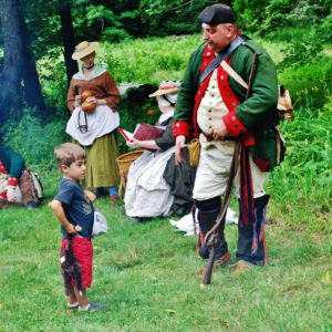 Reenactors and child Bidwell House Museum, two men and two women in 18th century costume, members of the Butler's Rangers reenactors at the 2017 Bidwell Country Fair, interact with a young visitor to the Museum