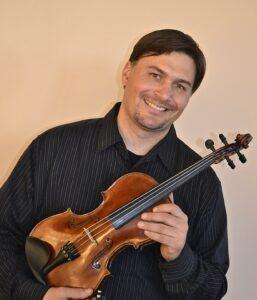 Violinist Eric Martin holding his violin